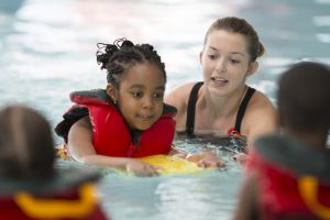 Swim Instructor Working with a Little Girl
